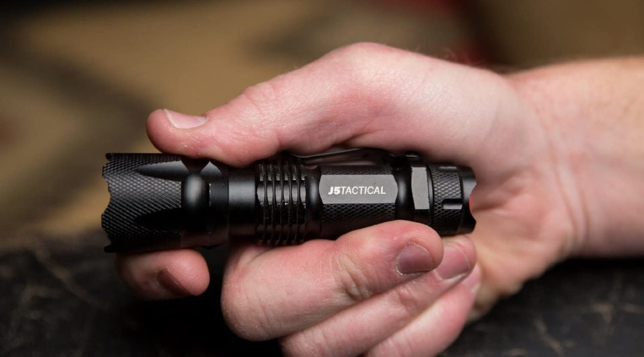 A tactical flashlight, color black, held by a hand.