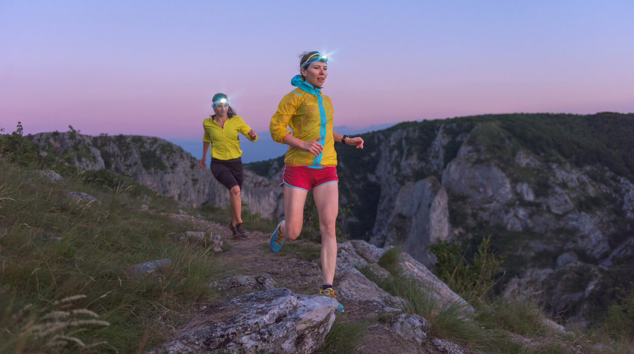 Image of two women runners wearing headlamps, sunset, on a mountain