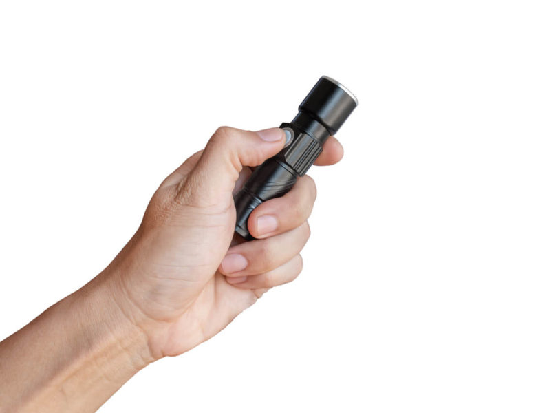 Image of a hand holding a small black flashlight