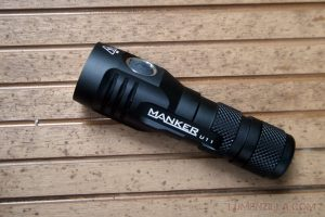 Image of the Manker flashlight in black color, lying on a woodplank.