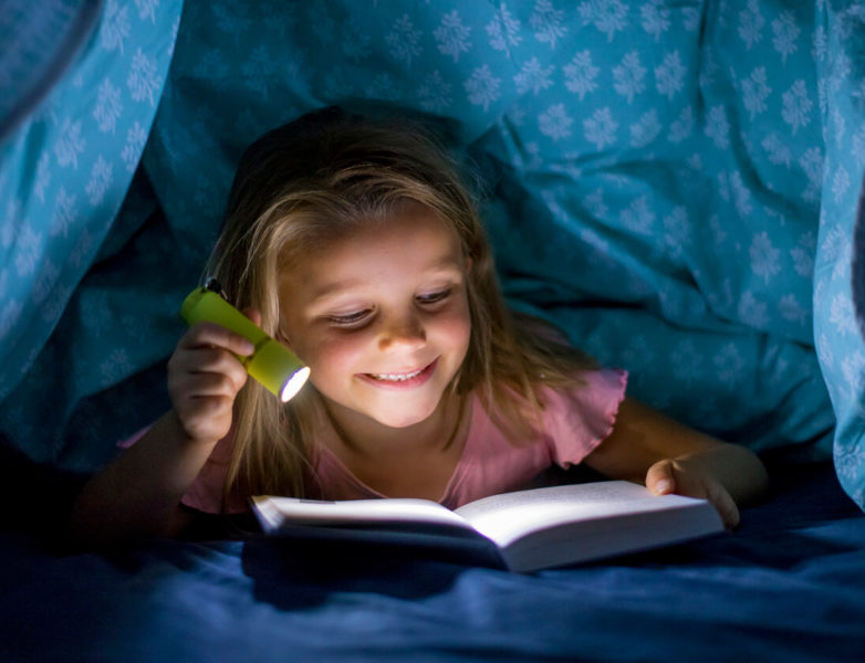 Image of a girl under a blanket holding a mini flashlight while reading a book.