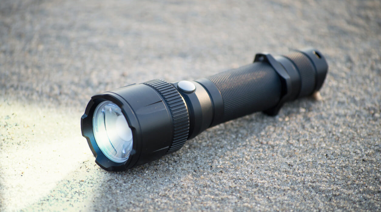 This is an image of a flashlight with light on, reflecting the surface where it was lying.