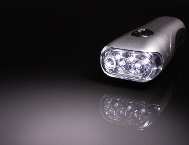 Image of a handcrank flashlight with reflection of its image on the shiny top..