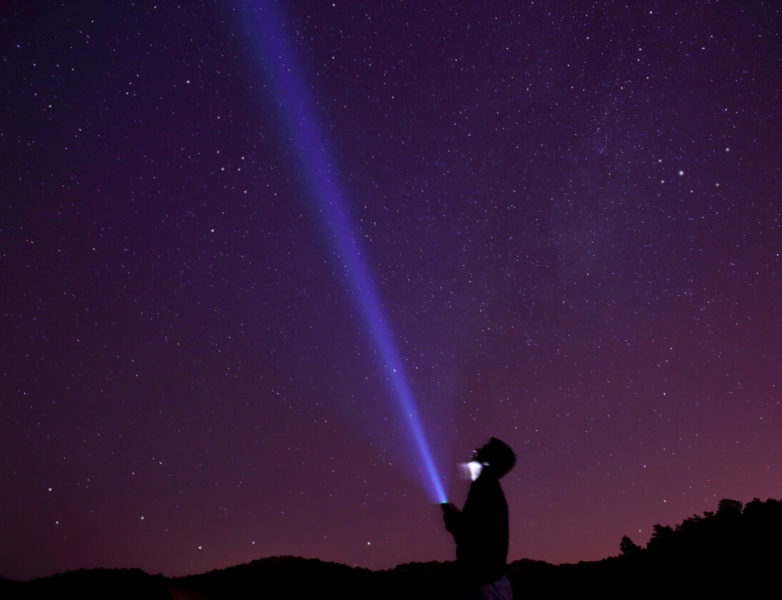 A man holding a flashlight at night with violet skies aiming the falshlight's beam above.