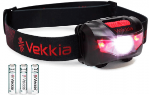 Photo of a headlamp with LED emitting a red and white beam, black-colored headband with brand name printed on it. Three batteries are seen below it.