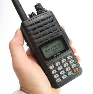 A photo of a hand holding a handheld radio with digital display and numeric keypads below it.