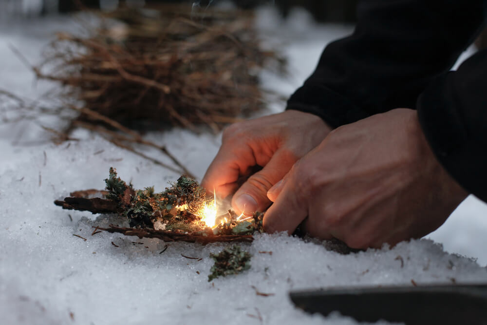 Image of a man holding a lighter trying to ignite a fire using dried leaves on an icy ground