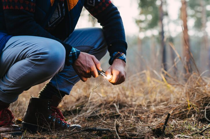A man makes a fire with a survival lighter