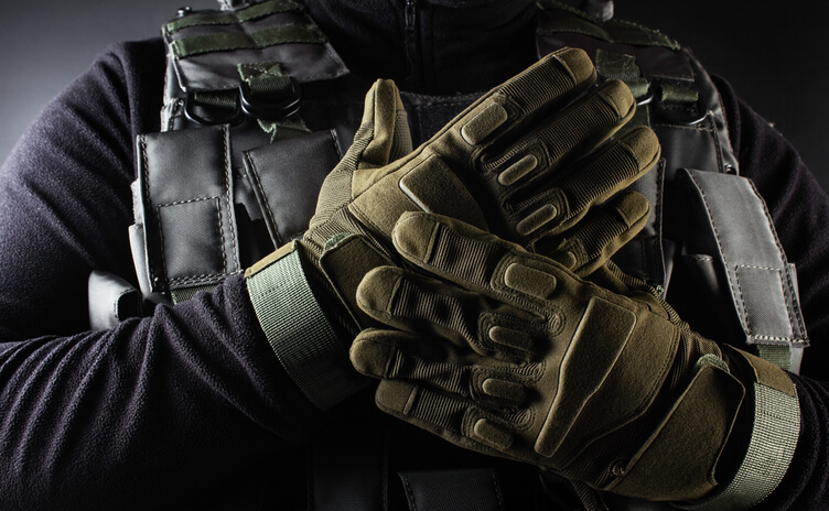 Photo of a fully equipped soldier in black armor tactical vest and gloves standing on black background closeup front view.