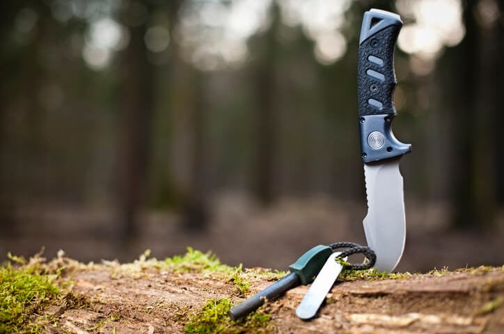 Schrade survival knive stuck in a piece of wood outdoors