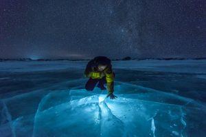 man using a flashlight. Milky Way on Ice Lake in Winter Grassland