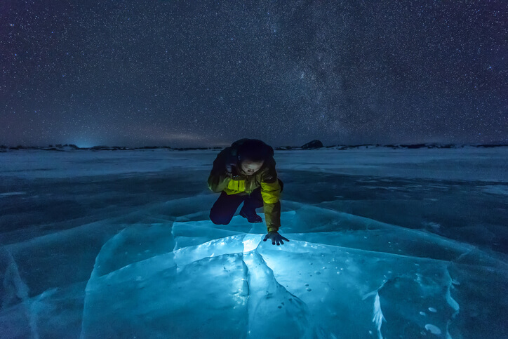 man using a flashlight. Milky Way on Ice Lake in Winter Grassland