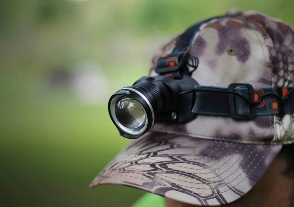 man wearing camouflage cap with hunting headlamp