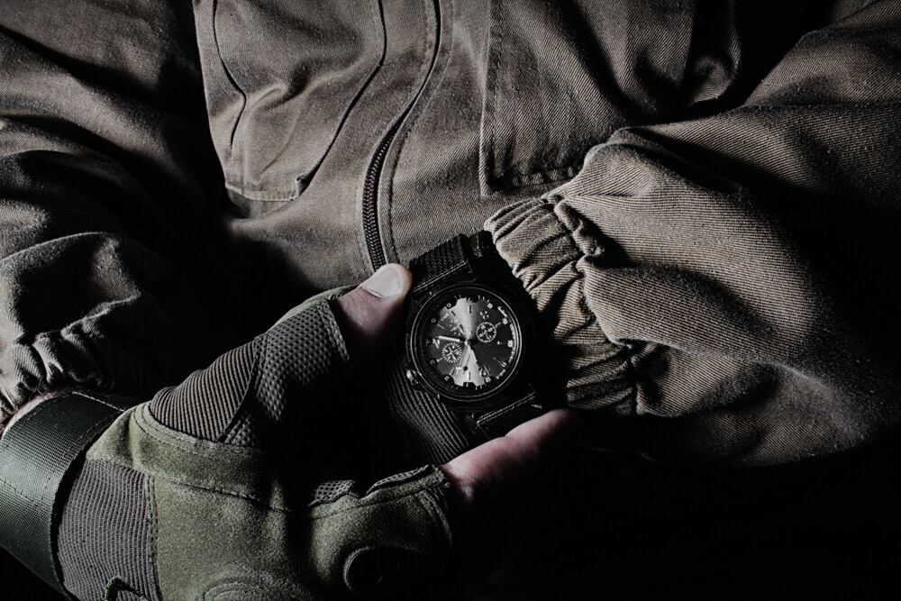 Profile view photo of a male person in brown tactical outfit jacket and gloves holding military watch on black background.