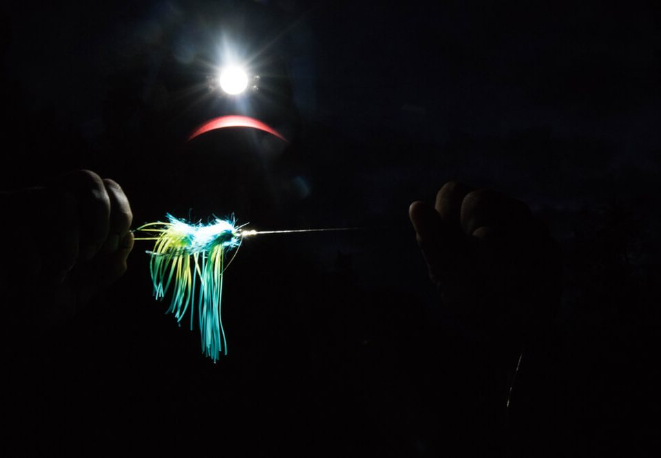 man shining his headlamp and Setting up a fishing line, Russian River, Alaska