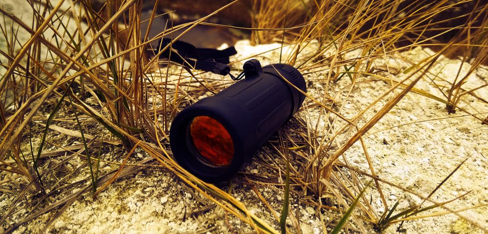 Monocular on the white sand in the mountains