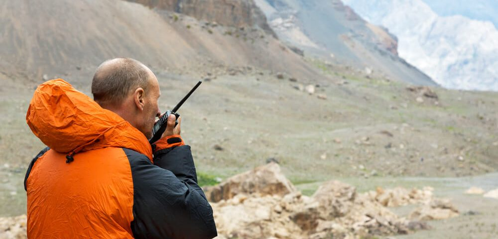 Man Talking on Yaesu FT 270R Radio. Mountain Rescue Officer Holding Radio Walkies Talkie and Severe Mountain Landscape Background