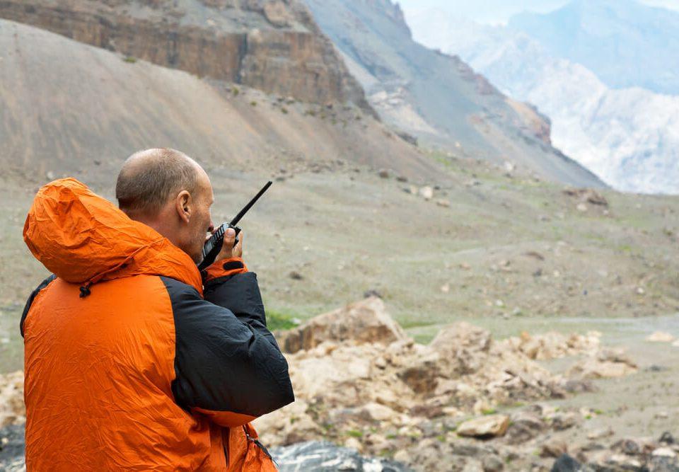 Man Talking on Yaesu FT 270R Radio. Mountain Rescue Officer Holding Radio Walkies Talkie and Severe Mountain Landscape Background
