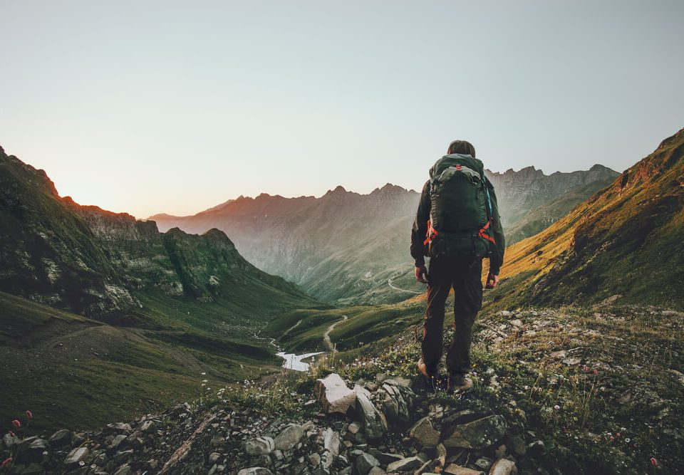 Man walking outdoor in nature with survival backpack on, beautiful scenery