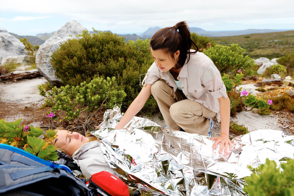 Medical emergency while hiking. woman has emergency blanket and her friend is calling for help