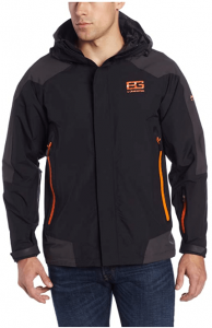 Image of a man wearing the Bear Grylls Men's Mountain Jacket in black color with orange outlines on both sids, a BG logo on the upper left-side.