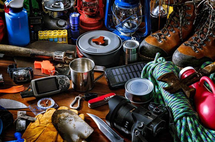 Survival, Camping and hiking themes: Top view of large group of gear, equipment and accessories for mountain trips and survival situations.