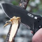 hand using a Zero Tolerance Knife cutting into a tree branch