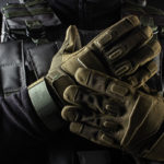 a pair of hands wearing a tactical gloves in green camo color.