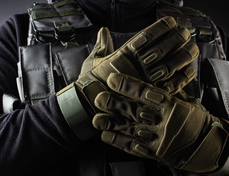a pair of hands wearing a tactical survival gloves in green camo color.