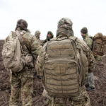 Photo of soldiers walking at the field wearing brown tactical backpacks.