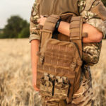a soldier standing on a field, holding a brown tactical vest.
