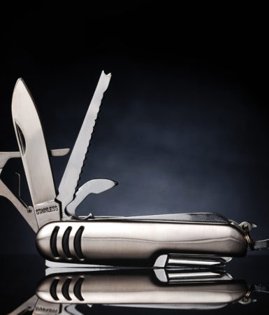 a multi-survival tool in silver color, against a black background,