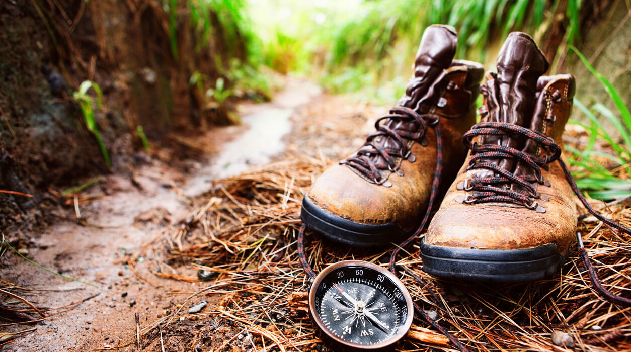 worn brown hiking boots, on a muddy trail with a compass.