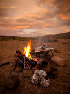 a camp fire, dusk with orange skies, burning logs on a campfire.