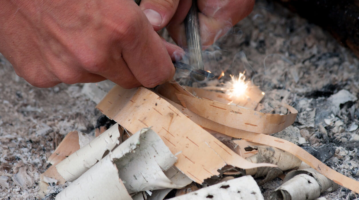 a man trying to start a fire using a tree bark and a flint on a rocky ground.