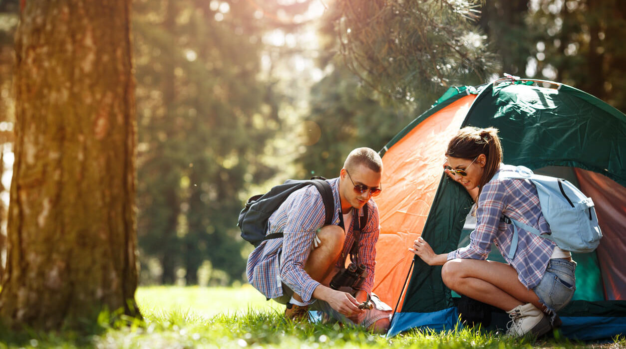 a young man and woman at the forest, setting up a color orange and blue tent.