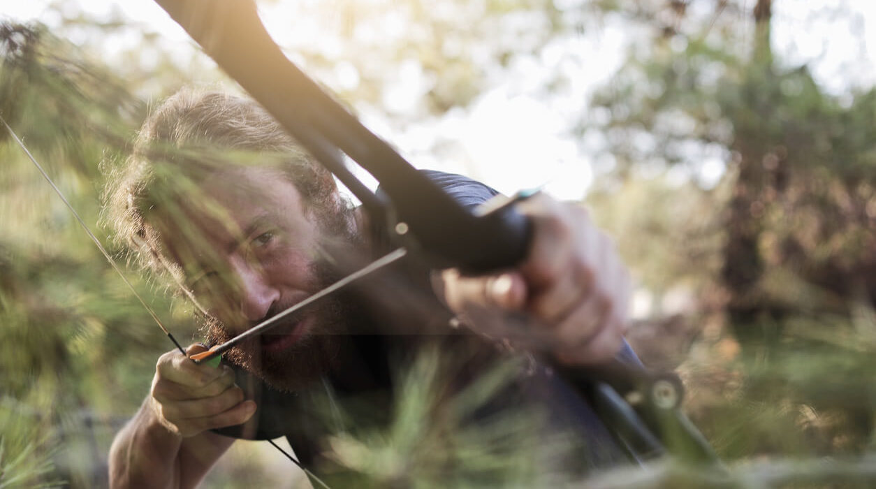 a young man is preparing to shoot with the survival bow in the forest