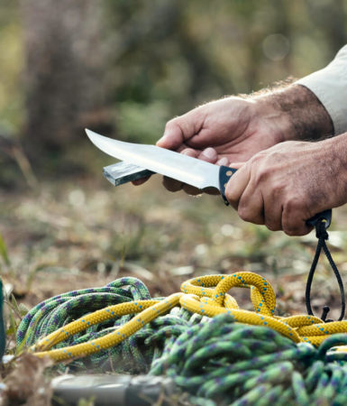 Man hands sharpening knife outdoors in the wilderness