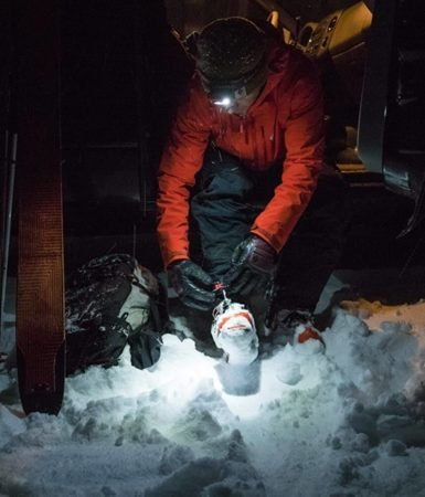 This is an image of a man fixing his shoelaces on an icy ground wearing the Black Diamond Storm at nighttime.