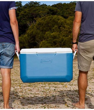 Two man walking and carrying the Coleman xtreme cooler in blue color, at the beach.