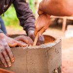 Close up photo of hands cooperating to build cement water well