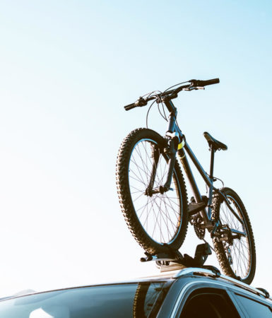 Photo of a bike on top of a car attached to a bike rack.
