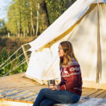 Photo of a woman drinking cofee while sitting near the canvass tent at the forest