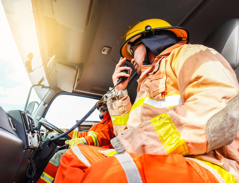 Photo of a firefighter using radio inside of a vehicle