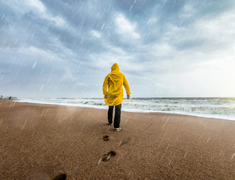 An image of a man wearing a coat and rain pants on a beach on a rainy day.