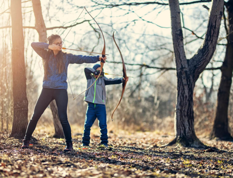 photo of children practicing shooting bows in forest