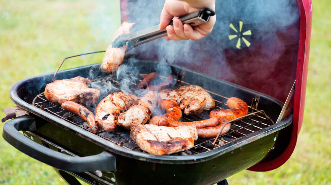Image f a barbeque grill with meat roasting on top.