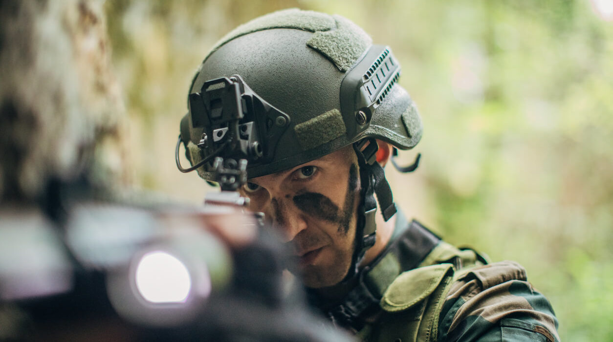 Military man wearing a tactical helmet, aiming a rifle.