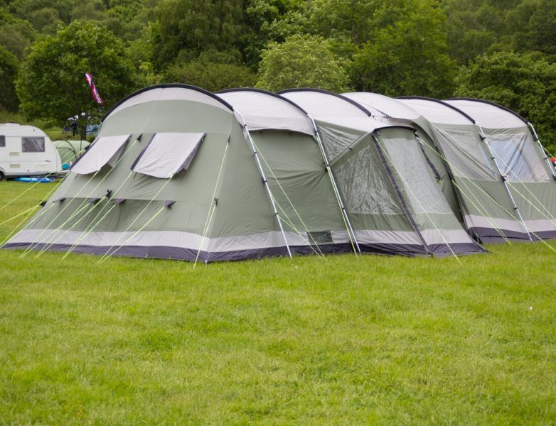 This is an image of a large, spacious tent in color moss green, on a grassy ground.