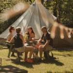 Photo of a family bonding outside a tent